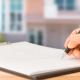 Erwerb einer Eigentumswohnung: Person unterzeichnet Kaufvertrag
