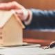 Ein Mann erklärt einen Vertrag und hat seine Hand auf ein Holzmodell einer Immobilie gelegt.
