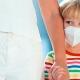 Eine Mutter hält ihr Kind an der Hand, was einen Mundschutz trägt