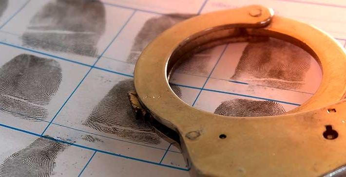 Handschellen, die auf einem Blatt mit Fingerabdrücken liegen