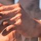 Eine Person hinter Gittern, die eine brennende Zigarette in der Hand hat.