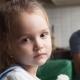 Unglückliches Kind mit Teddy vor unzufriedenen Eltern